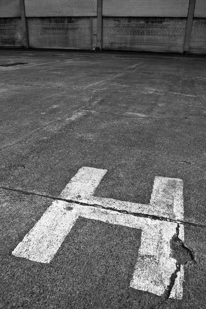 DE, DE-NW, K, NRW, airfield, asphalt, aviation, b&w, black and white, buchstabe, buchstaben, buildings, butzweilerhof, bw, cologne, deutschland, flugfeld, flugplatz, flugzeughalle, fotografie, gebäude, germany, hangar, köln, letter, letters, luftfahrt, nordrhein-westfalen, northrhine-westfalia, ossendorf, photography, schild, schilder, schwarzweiß, sign, signs, stadtbezirk 4 - ehrenfeld, sw, tarmac, world
